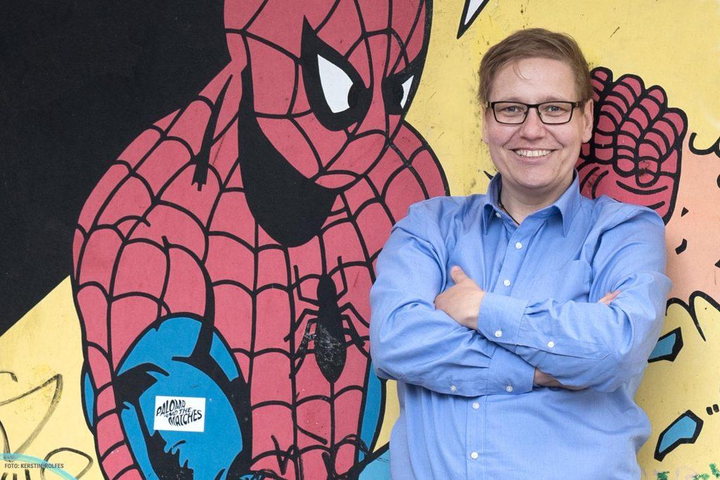 Freddy Wenner im blauen Hemd vor einer bemalten Hauswand. - Foto von Kerstin Rolfes.