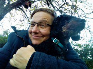 Ich halte einen in die Ferne blickenden Pudel im Arm und schaue breit lächelnd in die Kamera. Hinter mit ist ein Garten zu erahnen, am Baum über mir hängt ein Vogelhäuschen.